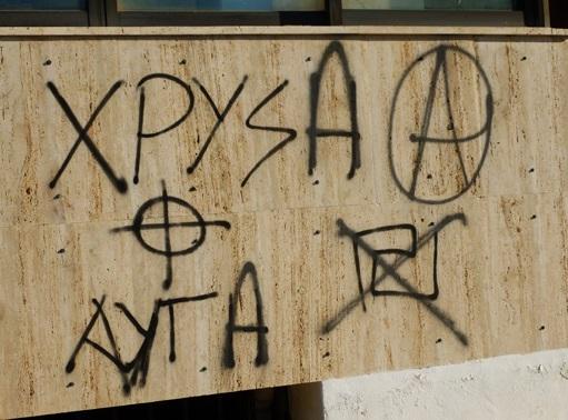 """Napisy """"Złoty Świt"""" na ulicach  pojawiają się coraz częściej. Tutaj ten sam napis został poprawiony na Hrisa Awha, czyli """"Złote Jaja"""". Korekta wykonana przez anarchistów."""
